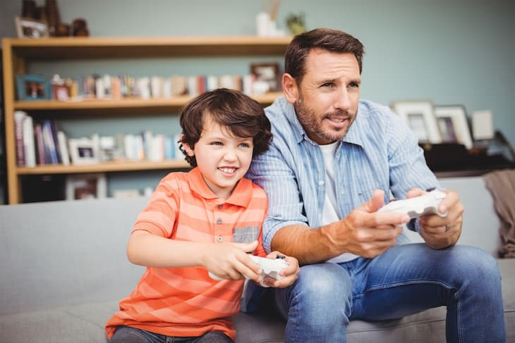 father with son playing computer game